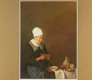 Een vrouw aan een gedekte tafel snijdt brood