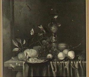 Stilleven van verschillende vruchten, een bord met een vis, een brood, en een roemer op een bekerschroef