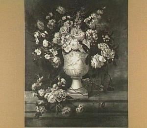 Boeket van verschillende bloemen in een gedecoreerde vaas, links een losse bos bloemen