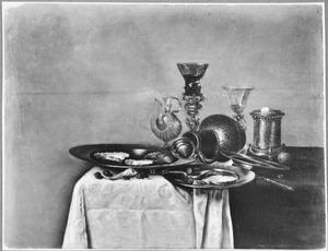 Stilleven met een bekerschroef, steengoed kan en oesters op tinnen borden