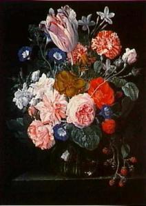 Bloemen en een tak bramen in een glazen vaas op een stenen plint