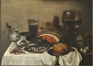 Stilleven met ham, wijn-en bierglazen, tinnen vaatwerk en bestek, brood, fruit, uitjes en faience-kruikje