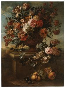 Bloemen in een geornamenteerde tuinvaas op een stenen piëdestal; op de grond liggen vruchten