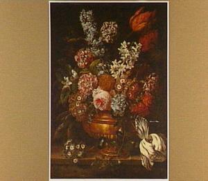 Boeket van bloemen in een bronzen urn op een natuurstenen richel