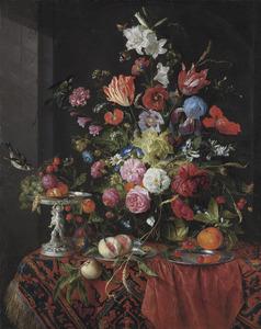 Bloemen in een glazen vaas en een zilveren tazza met fruit
