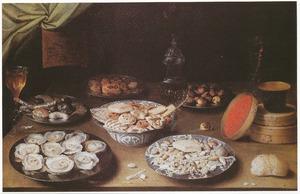 Stilleven met oesters, suikerwerk, brood en glaswerk