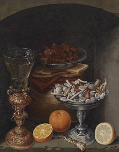 Stilleven met een berkemeier in een bekerschroef, sinaasappels en een tazza met suikerwerk in een nis