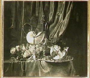 Pronkstilleven met nautillusbeker, vruchten, siervaatwerk en een horloge op een donker kleed en voor een draperie