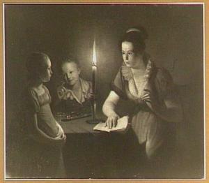 Jonge vrouw met twee kinderen rond een tafel bij kaarslicht