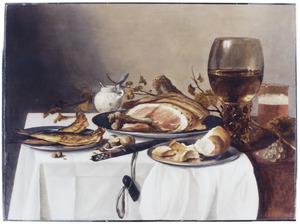 Stilleven van tinnen borden met ham, haring en brood, een roemer en een kruikje