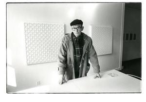 Portret van Jan Schoonhoven voor twee van zijn werken in Galerie Orez