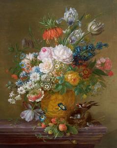 Bloemen in een gedecoreerde vaas met een vogelnestje