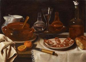 Stilleven met salami, sinaasappel, glas- en aardewerk op tafel met wit tafelkleed