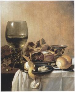 Een roemer, tinnen borden met een deels geschilde citroen en gebak, een broodje en een tazza op een met een wit kleed bedekte tafel