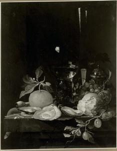 Oesters, vruchten en een roemer op een stenen tafel