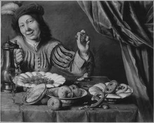 Een jongen houdt kersen op achter een tafel met een stilleven