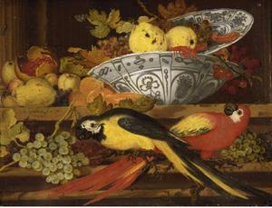 Stilleven met een porseleinen bord met vruchten op een porseleinen kom en twee papegaaien op een tak