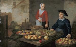 Marktkoopvrouw met een klant achter een tafel met manden met vruchten en groenten