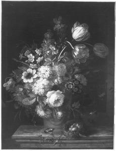 Bloemen in een vaas naast een vogelnest op een marmeren blad