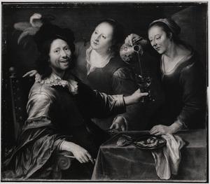 Twee vrouwen bedienen een aan een tafel zittende lachende man
