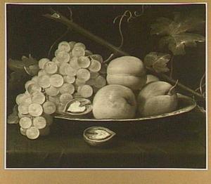 Stilleven van druiven en perziken op een platte porseleinen schotel
