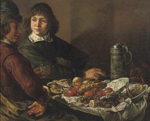 Twee jonge mannen met een eekhoorn aan een maaltijd met fruit en 'Pretzels'