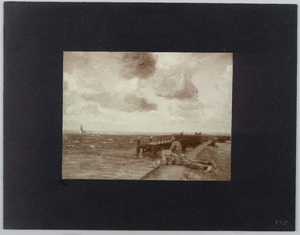 Liggende jongens op een kade aan zee