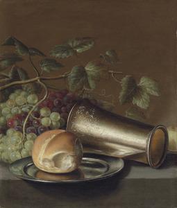 Stilleven met een brood op een tinnen bord, een gegreveerde zilveren beker, druiven en een pruim, op een stenen plint