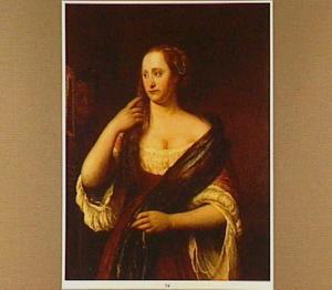Portret van een jonge vrouw kijkend in een door een bediende omhoog gehouden spiegel
