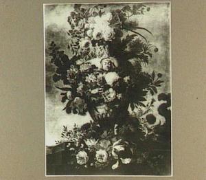 Bloemen gerangschikt om een urn op een stenen richel