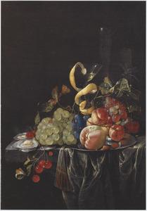 Stilleven met vruchten, een wijnglas met een citroenschil en oesters op een deels bedekte stenen tafel
