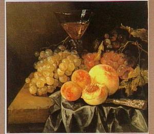 Stilleven met druiven, perziken en abrikozen, een wijnglas en mes op een donker kleed