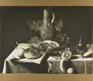 Stilleven met kruik, vlees, brood en vruchten op een tafel