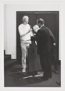 Jan Andriesse achter een microfoon met Hans Locher en Hans Janssen in Den Haag