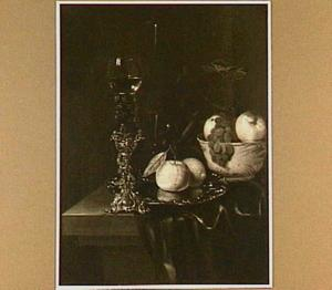 Stilleven met roemer in bekerschroef, siervaatwerk en vruchten op een tafel met donker kleed