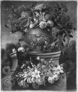Bloemen in en om een tuinvaas op een piedestal