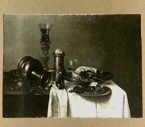 Stilleven met een bekerschroef, een liggende Jan Steen-kan, een zoutvat en tinnen schotels met oa. een pastei