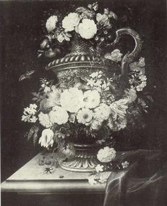 Bloemstilleven in en rondom een metalen vaas met oor op een tafel, rechts een teruggeschoven tafellaken