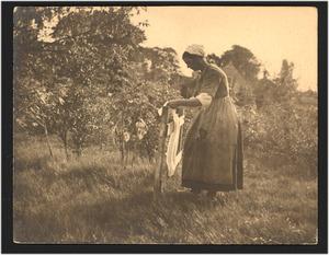 Boerenvrouw die de was te drogen hangt, vermoedelijk een model van de schilder Evert Pieters