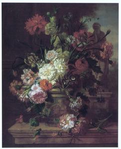 Bloemen in een pot op een balustrade voor een tuinbeeld