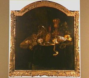 Stilleven met omgevallen tazza, akeleibeker, porseleinen schaal, vruchten, oesters en brood op een donker kleed