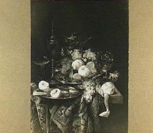 Stilleven met vruchten siervaatwerk en glaswerk op een tafel met oosters kleed