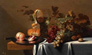 Stilleven op een tafel met rode en witte druiven, perziken op een tinnen bord, een half geschilde citroen in een roemer