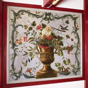 Vaas met bloemen omgeven door rocailles en vogels