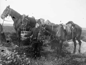 Militair met twee paarden tijdens een militaire manoeuvre