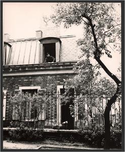 Karel Appel leunend uit een raam van zijn atelier aan de Rue Brézin, Parijs