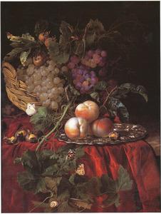 Stilleven van vruchten in een mand en op een gedreven zilveren schaal, op een rood kleed