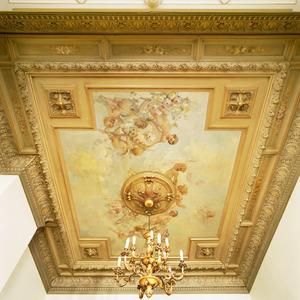 Stucplafond met middenveld waarin putti medaillons met kinderportretten vasthouden