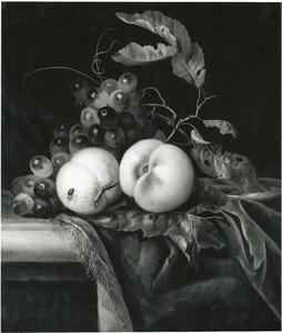 Stilleven van druiven en perziken op een deels met een kleed bedekte stenen plint