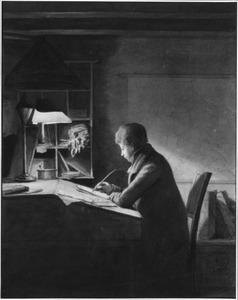 Jongeman in studeervertrek gezeten aan een schrijftafel